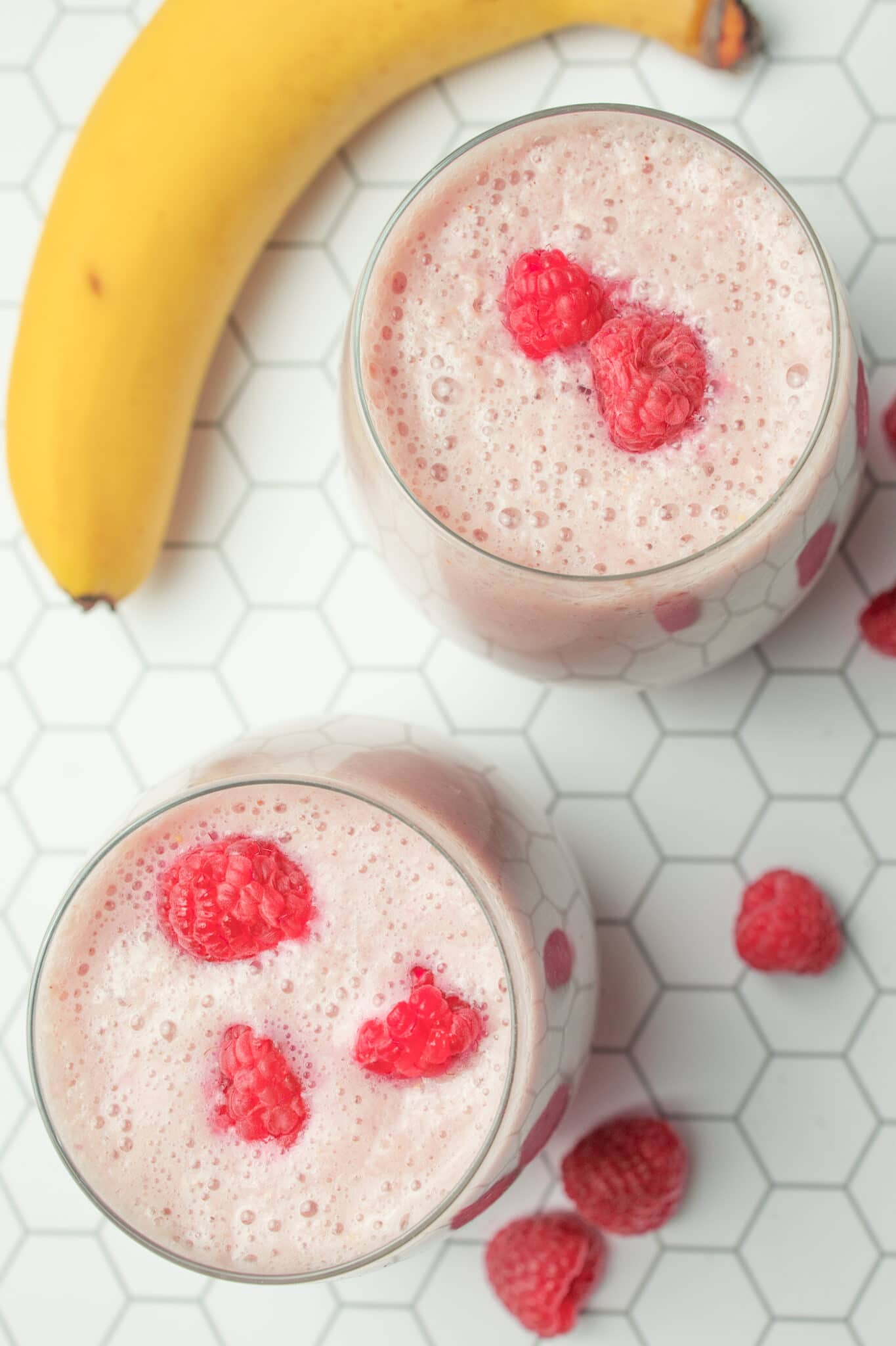 top down view of two glasses of banana raspberry smoothies with some raspberries and banana