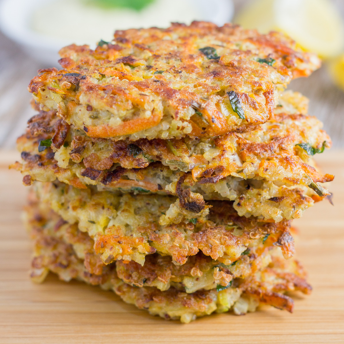 stack of quinoa fritters on a board with healthy garlic aioli in the background and lemon wedges