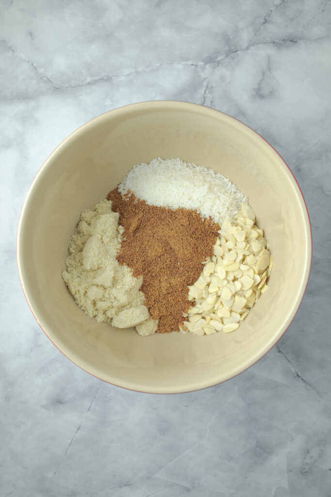 photo of the almond meal, shredded coconut, flaked almonds and coconut sugar added to a large mixing bowl