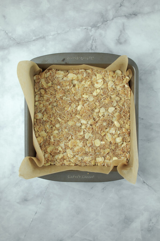 photo of the Anzac slice mixture smoothed over and ready to bake