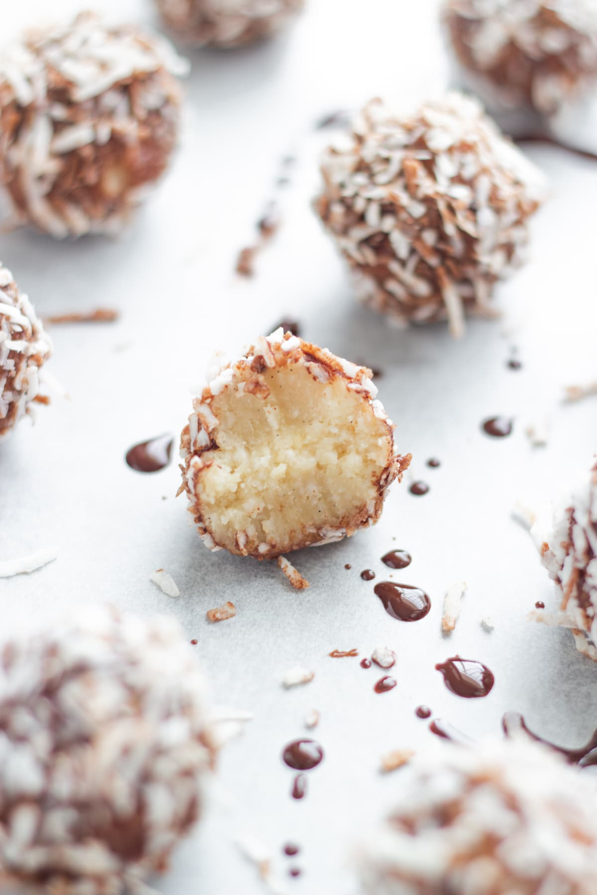 lamington bliss balls on a baking tray lined with baking paper with one of the bliss balls cut in half to show the inside