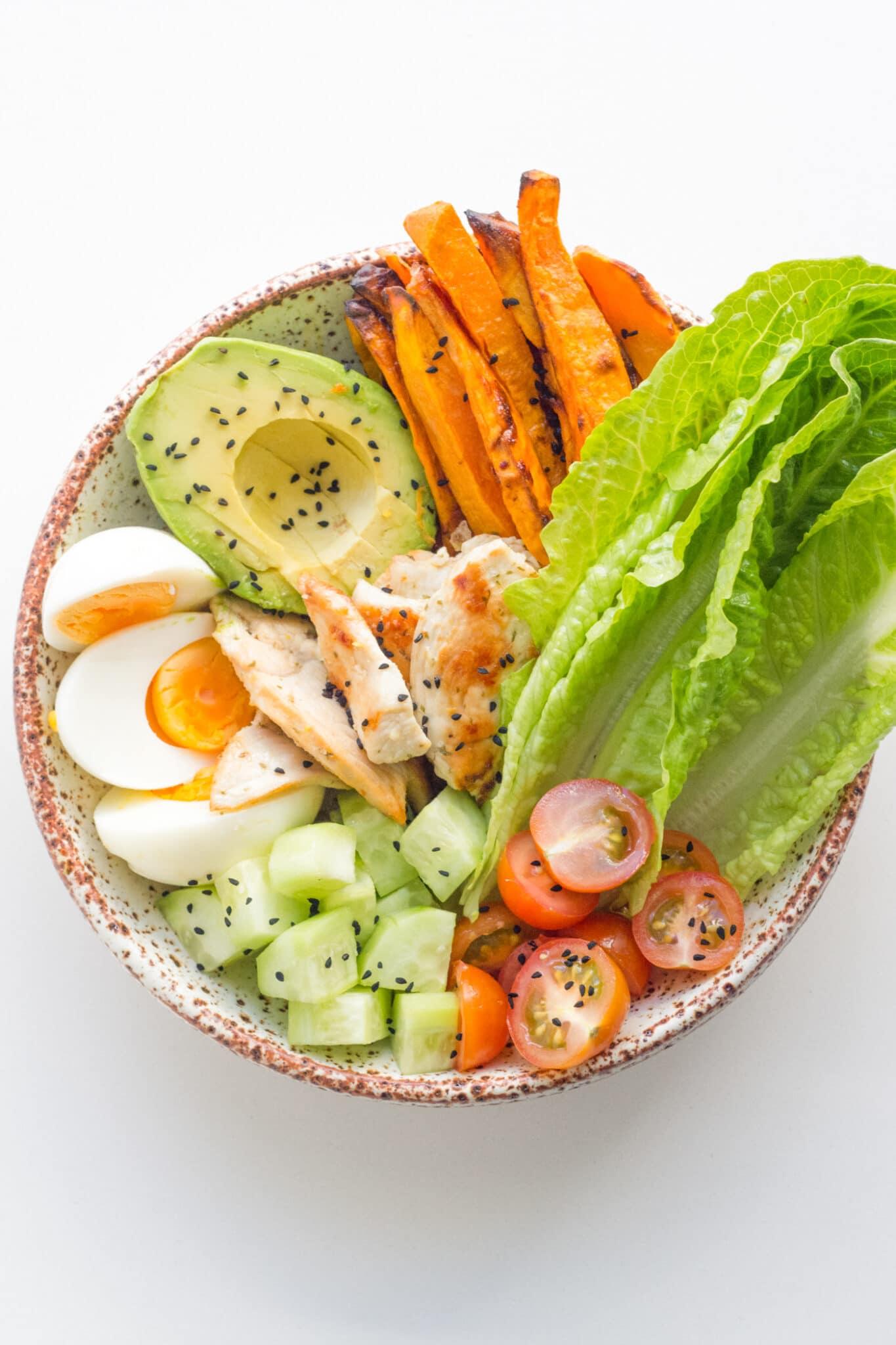 photo of the lemon garlic chicken buddha bowl with sweet potato, avocado, egg, cucumber, cherry tomato, lettuce and chicken.