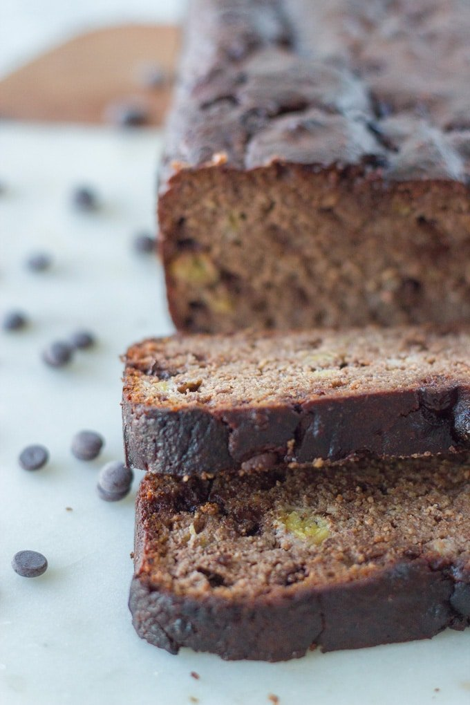gluten free chocolate banana bread on a ceramic/wooden board with a few slices cut in front