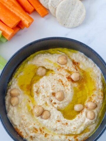 Super Easy 5 Minute Hummus. The easiest and tastiest hummus ever. Made with simple ingredients - chick peas, tahini, lemon juice, garlic, olive oil and cumin!