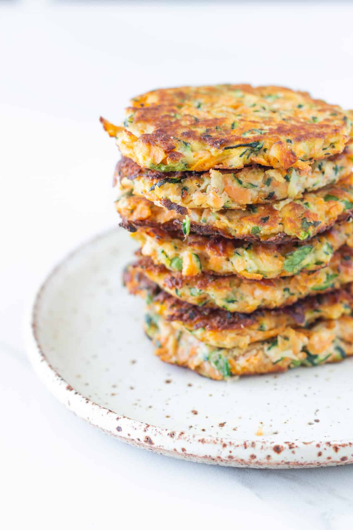 stack healthy zucchini and sweet potato fritters on a plate