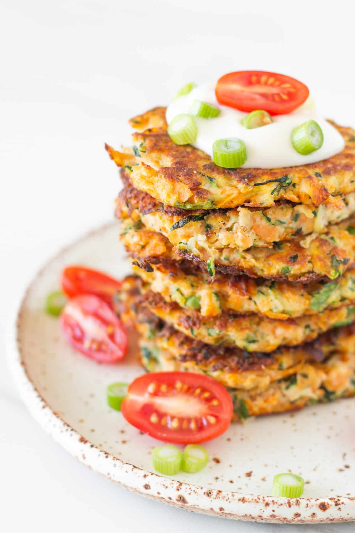 stack healthy zucchini and sweet potato fritters on a plate with aioli, cherry tomatoes and lemon wedges.