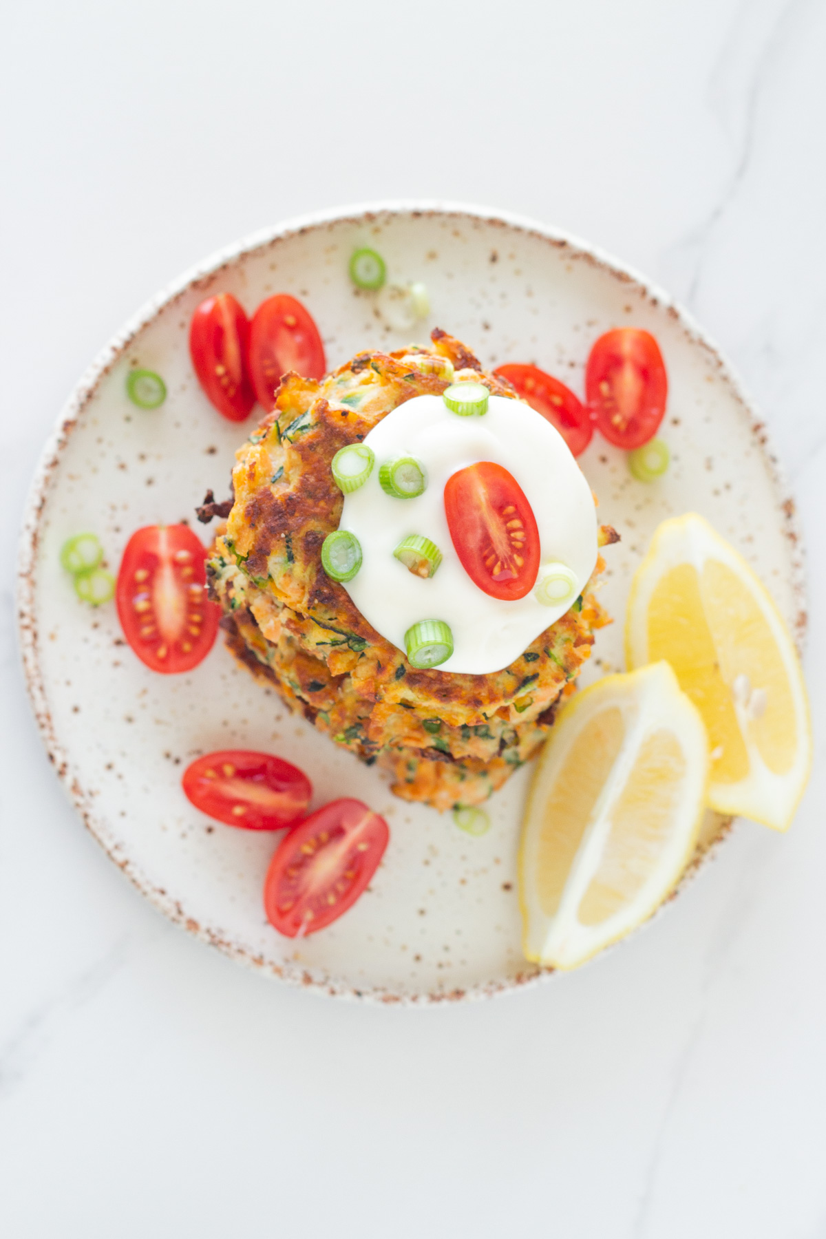 top down view of a stack healthy zucchini and sweet potato fritters on a plate with aioli, cherry tomatoes and lemon wedges.