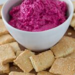 beetroot hummus in a bowl with crackers in front of it