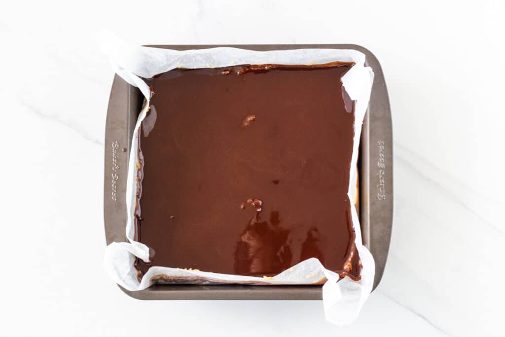 photo of the raw caramel slice with the chocolate layer just poured over the top.