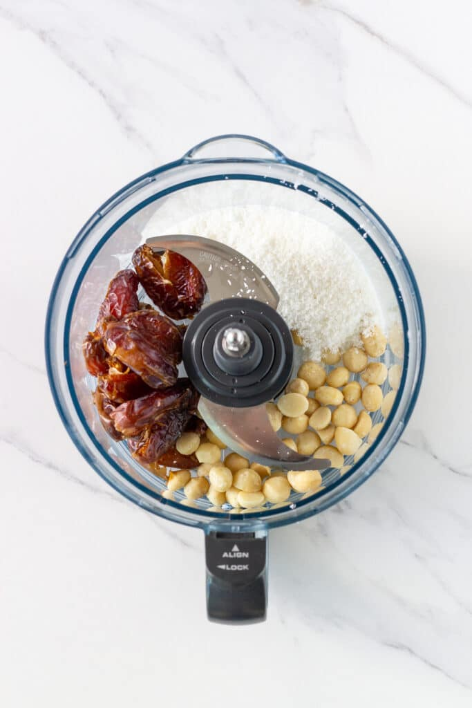 picture of food processor bowl with the base ingredients – dates, shredded coconut and macadamias.