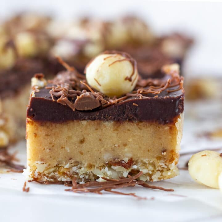 photo of a piece of raw caramel slice with the rest of the slice behind.