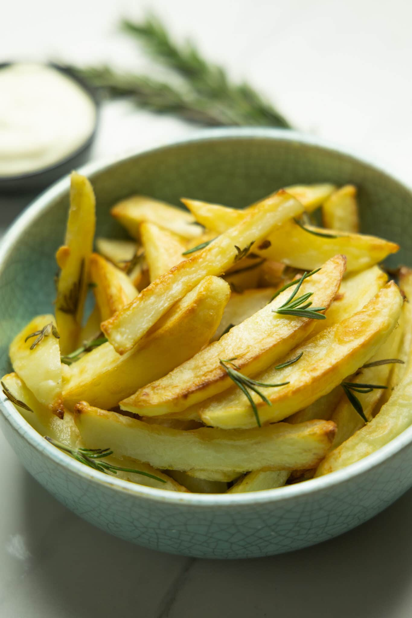 photo of the fries in a bowl with aioli and rosemary in the background