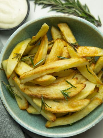 photo of a bowl of healthy oven baked fries with aioli and rosemary