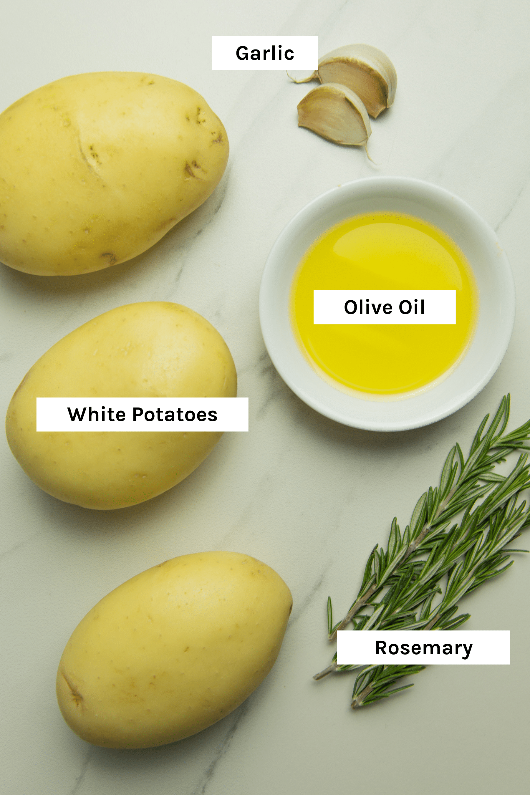 photo of the ingredients used to make these healthy oven baked fries - white potatoes, olive oil, garlic, rosemary and sea salt (which is missing from the image)