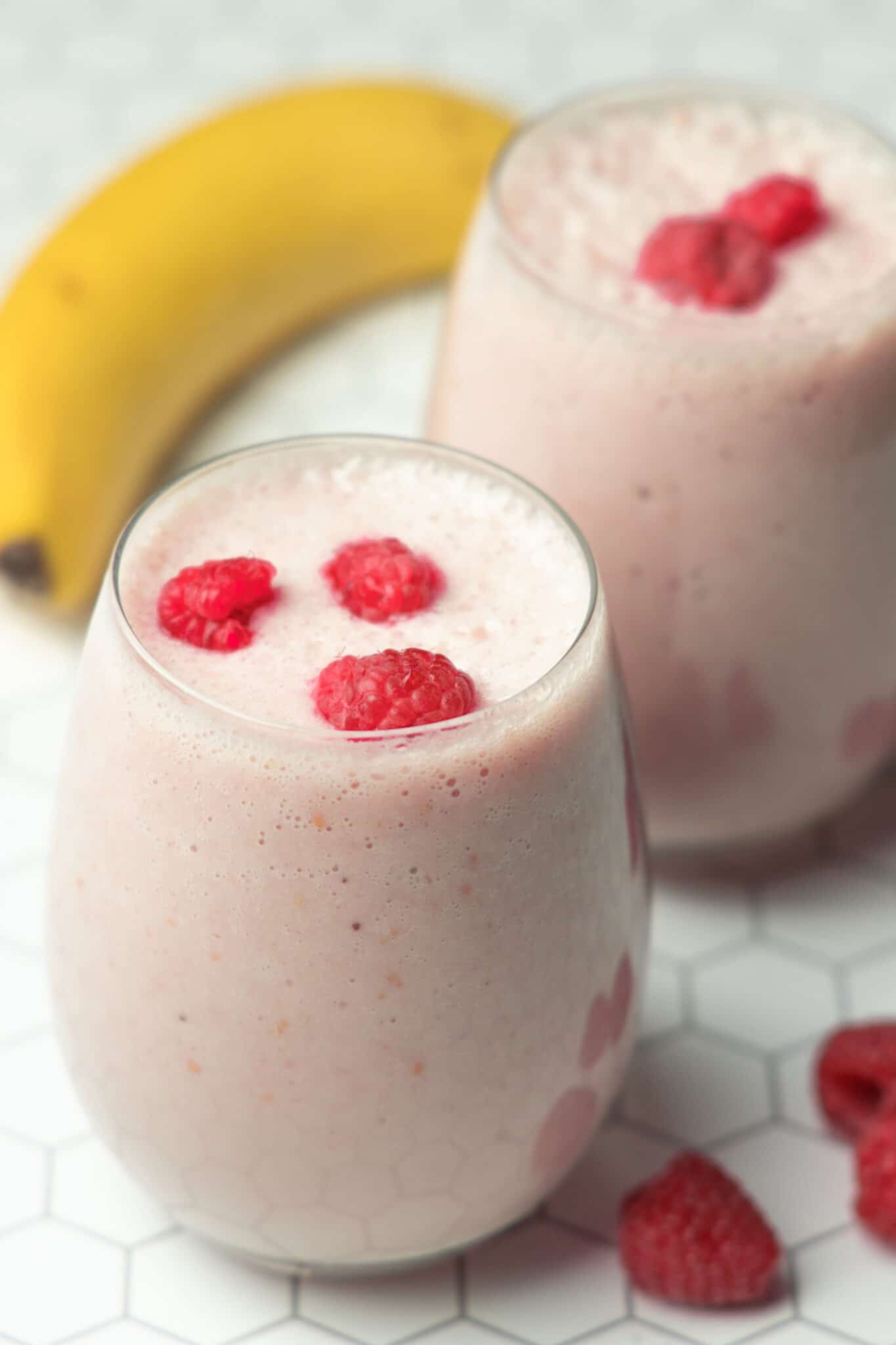 photo of two glasses of banana raspberry smoothies on a white tiled background with a banana and raspberries