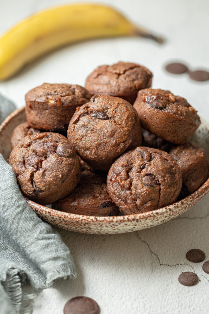 photo of a Bowl of Gluten Free Double Chocolate Banana Muffins next to a napkin, some chocolate chips and a banana in the background