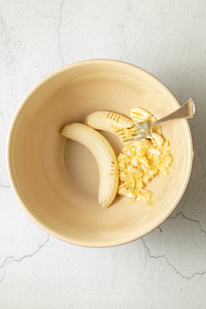 bowl with bananas that are being mashed with a fork