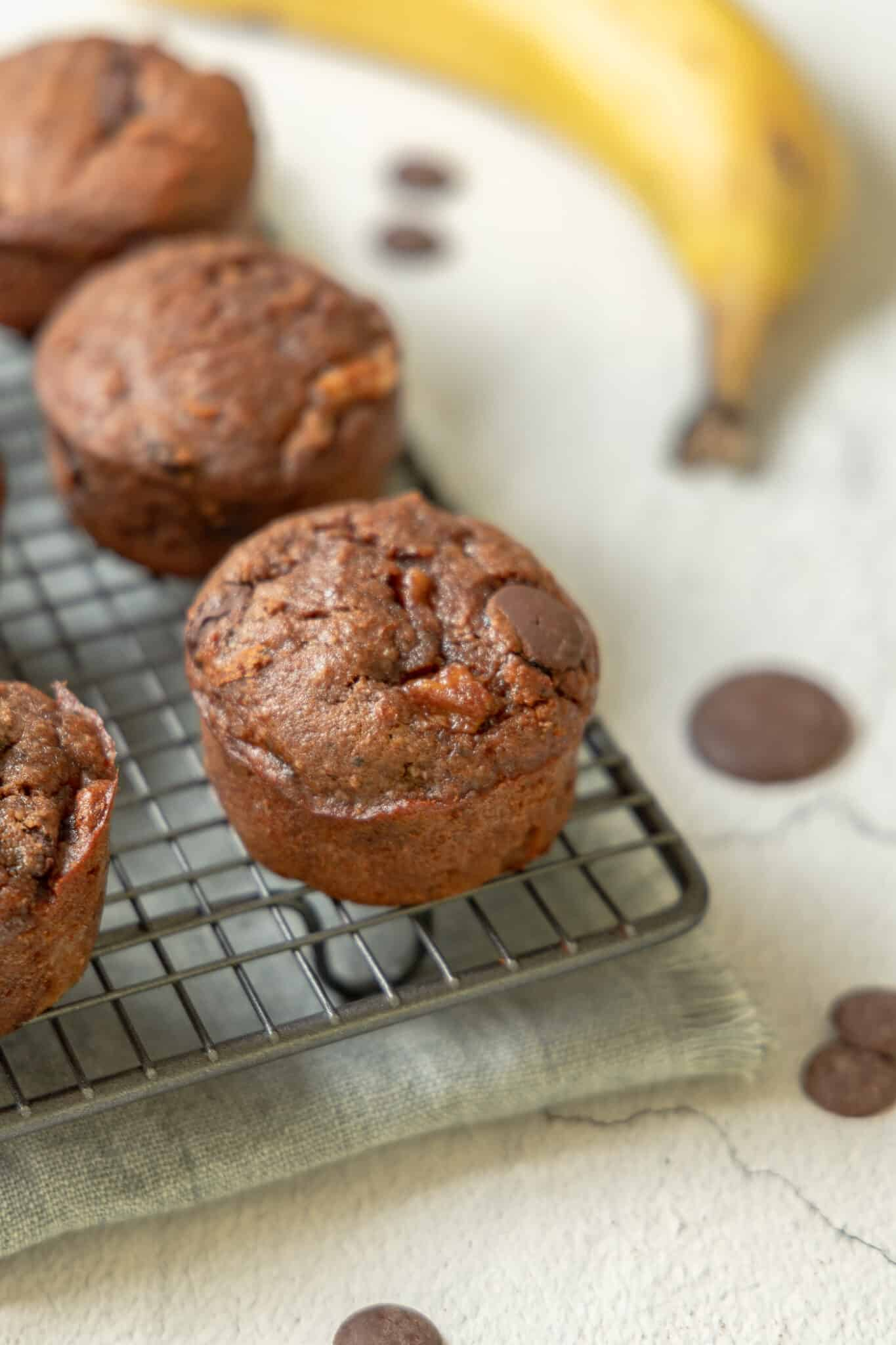 photo of a cooling rack of One Bowl Gluten Free Double Chocolate Banana Muffins on top of a grey napkin with some chocolate chips a banana in the image